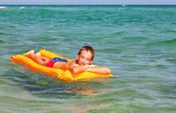 Boy on a inflatable mattress Stock Photos