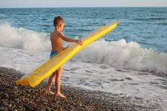 Boy with inflatable mattress stands on seacoast Royalty Free Stock Photo