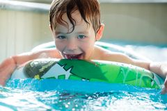 Boy in inflatable ring having fun. Cute boy in inflatable ring having fun in the swimming pool stock photography