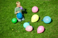 The boy inflates balloons, sitting on a grass Royalty Free Stock Photo