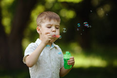 Boy inflates bubbles in summer park Royalty Free Stock Image