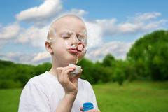 Boy inflates soap bubbles Royalty Free Stock Images