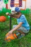 Boy inflates soccer ball pump Stock Image
