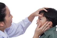 Boy with an injured eye. Little asian boy with an injured left eye. Doctor examining and first aid a patient. Child pain. Studio shot. On white background Royalty Free Stock Image