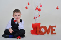 Boy with the inscription love. Sitting near the white tree with red hearts Stock Photos