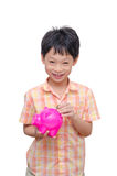 Boy inserting coin into piggy bank Royalty Free Stock Photo