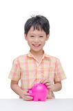 Boy inserting coin into piggy bank Stock Photo