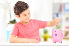 Boy inserting coins into a piggybank Stock Photography