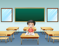 A boy inside a classroom with an empty board at the back Royalty Free Stock Image