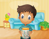 A boy inside the house with a jar of candies Stock Image