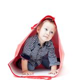The boy inside packet. Cute little boy inside a red packet. Concept of own toy house Royalty Free Stock Image