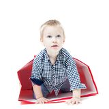 The boy inside packet. Cute little boy inside a red packet. Concept of own toy house Stock Photo