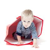 The boy inside packet. Cute little boy inside a red packet. Concept of own toy house Stock Photography