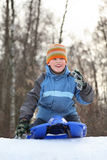 Boy intend drive from hill in winter on sledges Stock Images