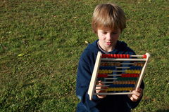 Boy interested in an abacus. Little boy that is interested in counting on an abacus royalty free stock image