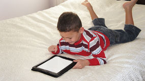 Boy with iPad. A boy laing on the bed playing on iPad royalty free stock photography