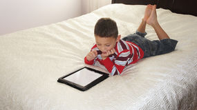 Boy with iPad. A boy laing on the bed playing on iPad Stock Image
