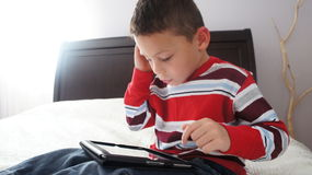 Boy with iPad. A boy siting on the bed playing on iPad stock photography