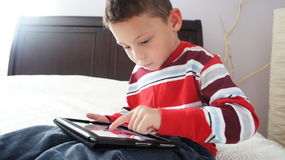 Boy with iPad. A boy siting on the bed playing on iPad stock photos