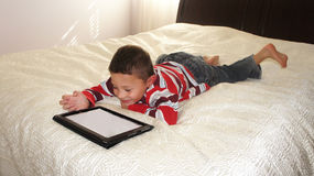 Boy with iPad. A boy laing on the bed playing on iPad stock photos