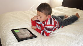 Boy with iPad. A boy laing on the bed playing on iPad royalty free stock photos