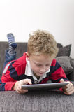 Boy on ipad. A boy playing on an ipad Royalty Free Stock Photography