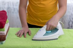 Boy irons towels on an Ironing Board Royalty Free Stock Images