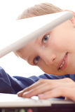 Boy ismiles and looks into the laptop. Beautiful boy smiles and looks into the laptop stock photography
