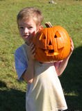 Boy and jack o' lantern. Proud little boy holding freshly carved jack o' lantern Stock Photo