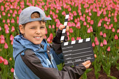 Boy in jacket and cap with cinema clapper board Royalty Free Stock Images