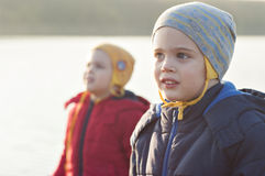 Boy in jacket and cap. With the twin-brother on background. Children dressed in different colors Stock Photos