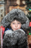 Boy in a jacket and a fur hat in Christmas with snowflakes Stock Image