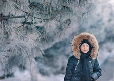 Boy in a jacket with a hood in a snowy park Stock Photography
