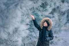 Boy in a jacket with a hood in a snowy park Royalty Free Stock Photo