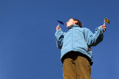Boy in jacket and pants blowing on pinwheels Stock Image