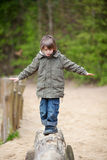Boy In Jacket Walking On Wood At Park Royalty Free Stock Photos