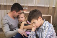 The boy is jealous of his father`s sister and sad. stock photos