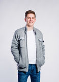 Boy in jeans and jacket, young man, studio shot. Teenage boy in jeans,  white t-shirt and jacket, young man, studio shot on gray background Royalty Free Stock Image