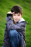 Boy in jeans sits on a grass Royalty Free Stock Images