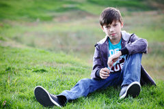 Boy in jeans sits on a grass. Boy in jeans smiles sitting on a grass Royalty Free Stock Photos