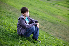 Boy in jeans sits on a grass. Boy in jeans smiles sitting on a grass Royalty Free Stock Images