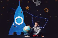 Boy in jeans and sneakers is sitting next to a toy rocket and a globe. NConstellation. Dream. Cosmonautn Stock Photography