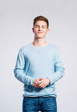 Boy in jeans and sweater, young man, studio shot. Teenage boy in jeans and blue sweatshirt, young man, studio shot on gray background Stock Images