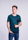 Boy in jeans and t-shirt, young man, studio shot. Teenage boy in jeans and green t-shirt, young man, studio shot on gray background Royalty Free Stock Photography