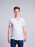 Boy in jeans and t-shirt, young man, studio shot. Teenage boy in jeans and white t-shirt, young man, studio shot on gray background Stock Photo