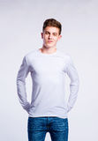 Boy in jeans and t-shirt, young man, studio shot. Teenage boy in jeans and white long sleeved t-shirt, young man, studio shot on gray background Royalty Free Stock Image