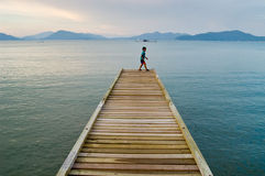 Boy on Jetty. Boy walking on a jetty in Pangkor Island,Malaysia Stock Photo