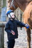 Boy Jockey caring for their horse Stock Image