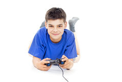 Boy the joystick while lying on the floor Stock Photography