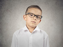 Boy with judgmental face expression. Closeup portrait skeptical boy with glasses looking carefully suspicious, skepticism on face, disapproval isolated grey Stock Photography